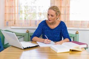 Eine junge Studentin beim lernen für ihr Studium in ihrer Wohnung.